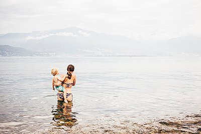 Rear view of mother standing in lake holding boy looking away at view of mountain range, Luino, Lombardy, Italy - p429m1105743 by JFCreatives