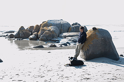 Mid adult man with dog leaning against boulder gazing at sea, Cape Town, Western Cape, South Africa - p429m1519635 by Bettina Mare Images