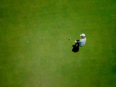 Man playing golf on golf course - p429m2164657 by Innocenti