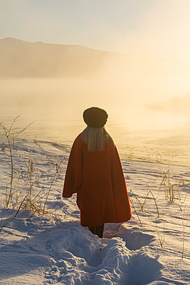 Caucasian woman standing in winter landscape at sunset - p555m1232042 by Steve Smith