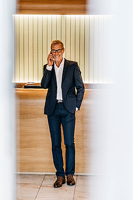 Mature businessman using mobile phone  - p586m1208624 by Kniel Synnatzschke