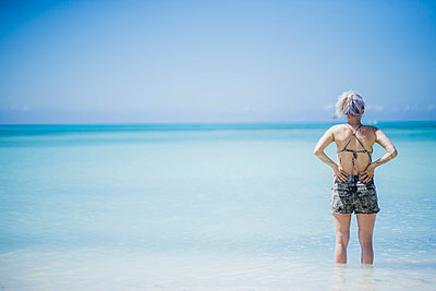 Rear view of woman standing in blue sea looking out, Angochi, Aruba, Lesser Antilles - p924m1469016 by Celeste Martearena
