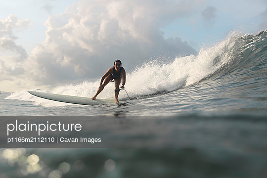 Low angle view of woman surfing in sea against sky - p1166m2112110 by Cavan Images