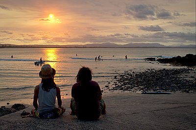 Two seated adults watching surfers at sundown - p1125m2073236 by jonlove