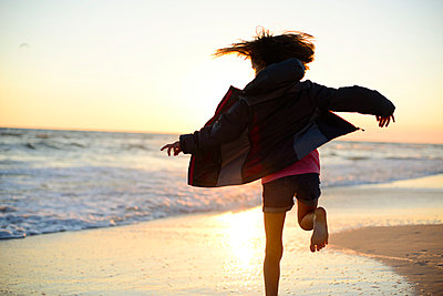 Rear view of playful girl running on shore against clear sky during sunset - p1166m1486189 by Cavan Images