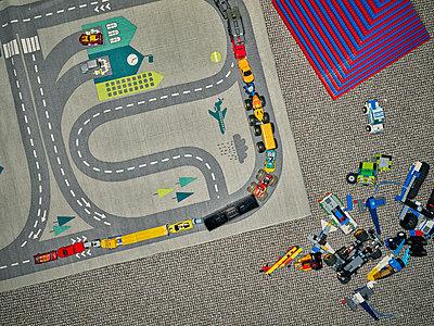 Toy cars on carpet in nursery - p1171m1540447 by SimonPuschmann