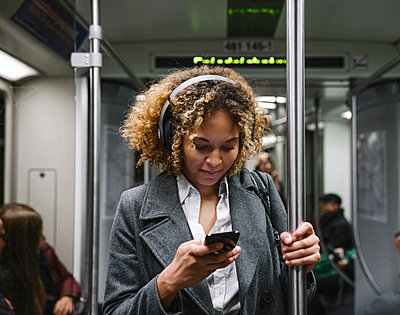 Woman using smartphone on a subway - p300m2143423 von Hernandez and Sorokina
