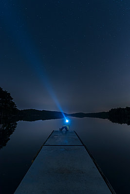 Person with headlight on jetty - p312m1470772 by Mikael Svensson