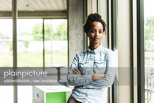 Confident young businesswoman leaning on window in modern office - p300m2004246 von Uwe Umstätter