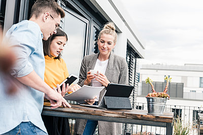 Casual business people meeting on roof terrace - p300m2132543 by Uwe Umstätter