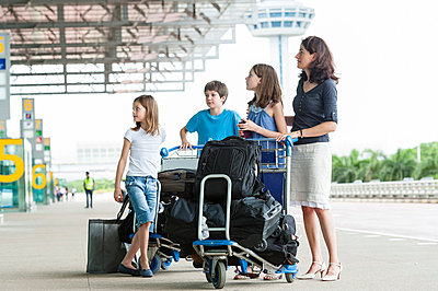Family standing outside of airport with luggage - p623m659179f by Thierry Foulon