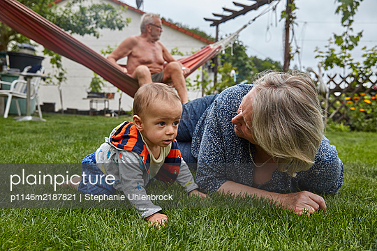 Grandparents with grandson in the garden - p1146m2187821 by Stephanie Uhlenbrock