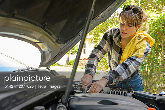 Woman repairing her car - p1427m2077625 by Tetra Images