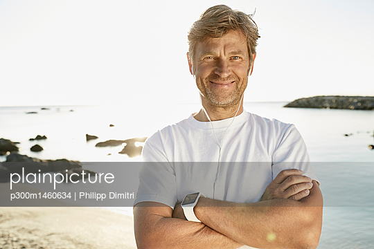 Portrait of smiling mature man with smartwatch and earphones on the beach - p300m1460634 by Philipp Dimitri
