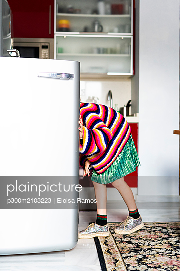 Girl in striped pullover in kitchen at home looking in fridge - p300m2103223 by Eloisa Ramos