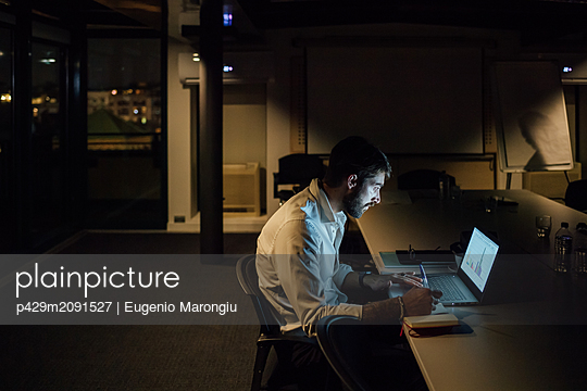 Mid adult businessman in office at night looking at laptop - p429m2091527 by Eugenio Marongiu