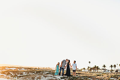 Family holding hands at beach as dad kisses mom - p1166m2207841 by Cavan Images