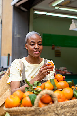 Woman buying tangerines in a market hall - p300m2179897 by VITTA GALLERY