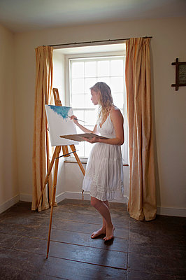 Young woman painting by window - p4296366 by Frank and Helena