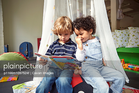 Children (2-3, 4-5) looking at book