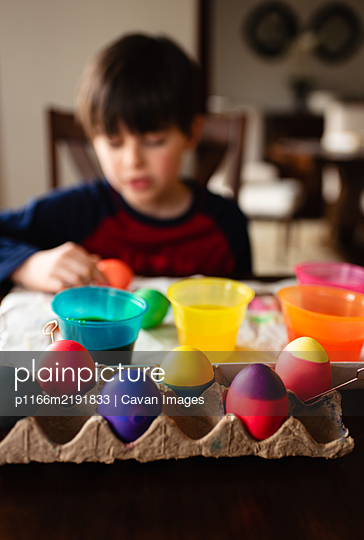 Colorful Easter eggs with boy dying them in the background. - p1166m2191833 by Cavan Images