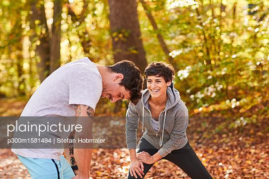 Couple stretching in autumn forest - p300m1581494 von Stefan Hobmaier