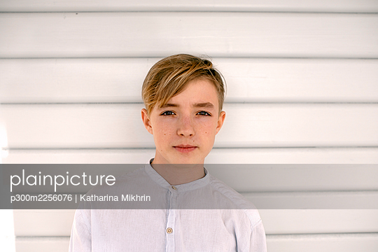 Thoughtful boy standing against white wall - p300m2256076 by Katharina Mikhrin