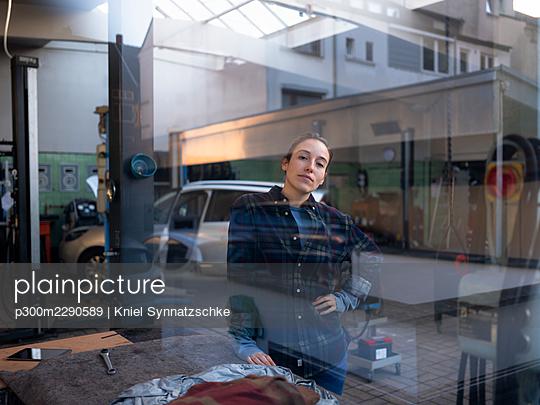 Female mechanic standing at car repair shop seen through window - p300m2290589 by Kniel Synnatzschke