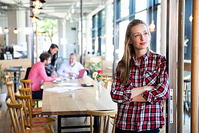 Portrait of casual businesswoman in a cafe with colleagues having a meeting in background - p300m2140367 by Florian Küttler