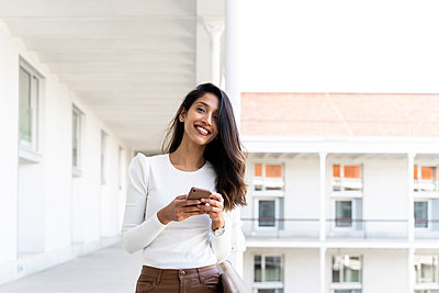 Smiling young woman holding smartphone on balcony - p300m2166204 by VITTA GALLERY