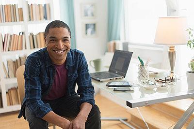 Black businessman smiling at desk - p555m1412822 by JGI/Tom Grill