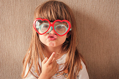 Portrait of girl wearing novelty glasses while puckering against wall - p1166m1493040 by Cavan Images