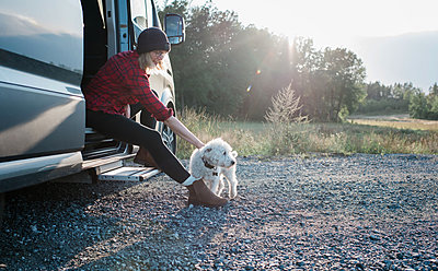 woman sitting on a camper van stroking her dog whilst camping - p1166m2136333 by Cavan Images