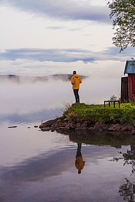 Lonely an standing at lake, looking at the fog - p300m2042411 by Kike Arnaiz