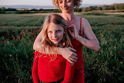 Mother stroking daughte's hair, standing in a poppy field - p300m2114824 von Oxana Guryanova