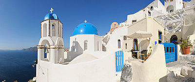 View of classical whitewashed church and bell tower at Oia - p300m731259f by Martin Rügner