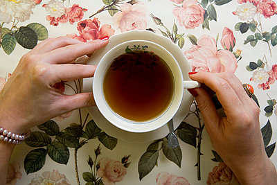 A woman drinking a cup of tea - p3016833f by Serge