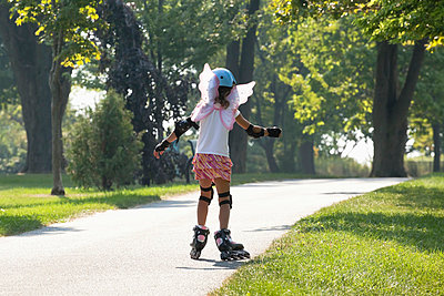 Young girl learning to inline skate while wearing fairy wings;Whitby ontario canada - p442m839773 by Mary Ellen McQuay