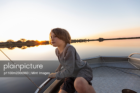 A young boy fishing from a boat on the flat calm waters of the Okavango Delta at sunset - p1100m2300960 by Mint Images
