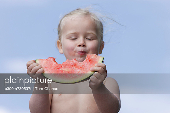 Girl eating piece of watermelon - p300m730537f by Tom Chance