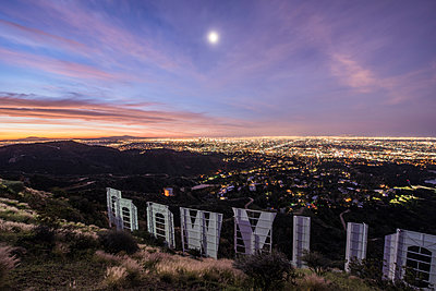High angle view of Hollywood sign by illuminated city at dusk - p1166m1193935 by Cavan Images