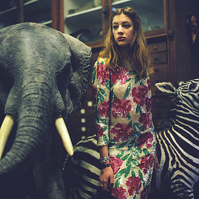 Girl standing in between a stuffed elefant and zebras - p1610m2186025 by myriam tirler