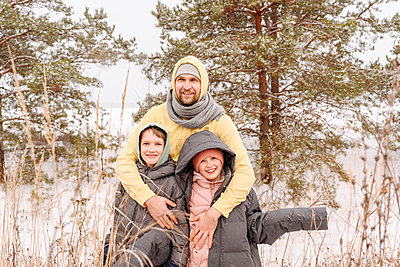 Father embracing son and daughter while standing against trees in forest during winter - p300m2251208 by Ekaterina Yakunina