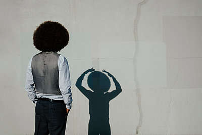 Young man with afro watching gesturing shadow on sunny wall - p301m2075537 by Sven Hagolani