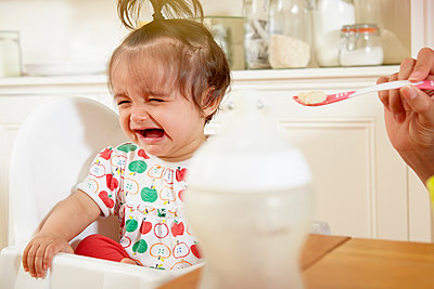 Baby girl crying while being fed breakfast by mother - p429m1417703 by Emma Kim