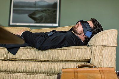 Caucasian businessman napping on sofa - p555m1459517 by Eric Raptosh Photography