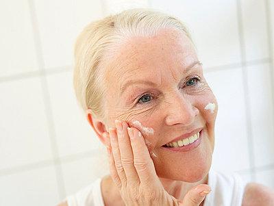 Aeltere Frau beim Eincremen  - p6430350f von senior images RF