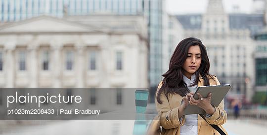 Businesswoman using digital tablet on city bridge - p1023m2208433 by Paul Bradbury