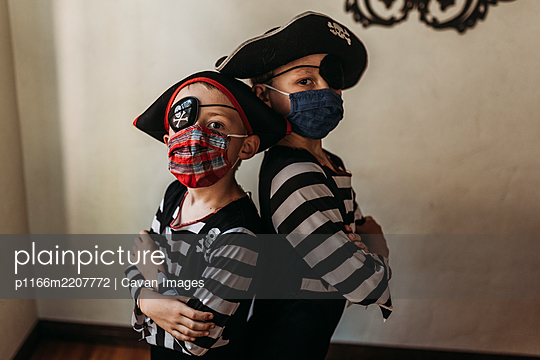 School age brothers dressed as pirates with face masks on - p1166m2207772 by Cavan Images