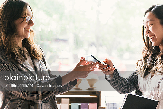 Close up of woman paying for purchase in small business with mobile - p1166m2285774 by Cavan Images